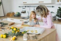 Νέα οικογένεια που κατασκευάζει τα μπισκότα στο σπίτι τρόφιμα, οικογένεια, Χριστούγεννα, hapiness και έννοια ανθρώπων - χαμογελών Στοκ Εικόνες