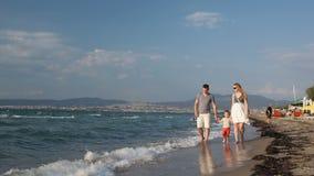 Νέα οικογένεια που περπατά στην παραλία φιλμ μικρού μήκους