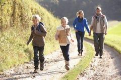 Νέα οικογένεια που περπατά στο πάρκο στοκ φωτογραφίες