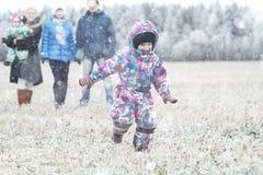 Νέα οικογένεια που περπατά στο χειμερινό τομέα με τα παιδιά Στοκ Φωτογραφία