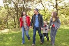 Νέα οικογένεια που περπατά υπαίθρια μέσω του πάρκου στοκ εικόνες