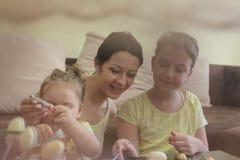 Νέα οικογένεια που χρωματίζει τα αυγά Πάσχας στοκ εικόνες