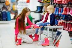 Νέα οικογένεια τριών που επιλέγουν τις νέες μπότες βροχής Στοκ Φωτογραφία