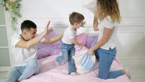 Νέα οικογένεια: mom ο μπαμπάς και λίγος γιος έχουν την πάλη μαξιλαριών διασκέδασης στο κρεβάτι απόθεμα βίντεο