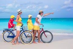 Νέα οικογενειακά οδηγώντας ποδήλατα σε μια τροπική παραλία Στοκ Εικόνες