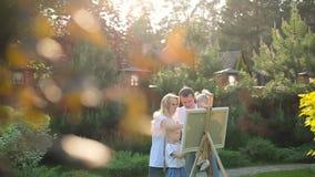 Νέα οικογενειακή ζωγραφική easel στον κήπο φιλμ μικρού μήκους