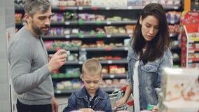 Νέα οικογενειακοί μητέρα, πατέρας και παιδί και επιλογή των γλυκών στο κατάστημα τροφίμων, παίρνοντας τα προϊόντα και εξετάζοντας απόθεμα βίντεο