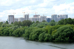 Νέα οικοδόμηση κτηρίου στη νέα περιοχή μετά από τον ποταμό πέρα από τον ουρανό με τα άσπρα σύννεφα στη θερινή ημέρα Στοκ Φωτογραφία