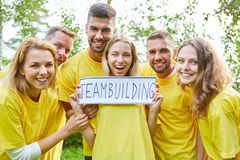 Νέα ομάδα ξεκινήματος με ένα teambuilding σημάδι στοκ φωτογραφία
