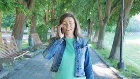 Νέα πάροδος πάρκων περπατήματος γυναικών που μιλά στο smartphone όμορφο περπάτημα πάρκων κορ& απόθεμα βίντεο