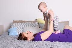Νέα παιχνίδια μητέρων με την λίγο μωρό στο κρεβάτι Στοκ εικόνες με δικαίωμα ελεύθερης χρήσης