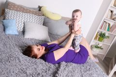 Νέα παιχνίδια μητέρων με την λίγο μωρό στο κρεβάτι Στοκ Εικόνες
