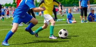 Νέα παιδιά παιδιών αγοριών που παίζουν το παιχνίδι ποδοσφαίρου ποδοσφαίρου Στοκ φωτογραφία με δικαίωμα ελεύθερης χρήσης