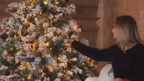 Νέα παραμονή έτους ` s, το κορίτσι το χριστουγεννιάτικο δέντρο και εστία στις οποίες τα αναμμένα κεριά, εορτασμός γυναικών απόθεμα βίντεο