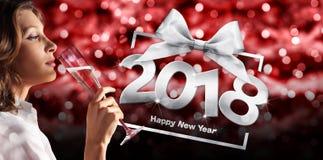 Νέα παραμονή έτους ` s φρυγανιάς, κρασί σπινθηρίσματος κατανάλωσης γυναικών στο κόκκινο που θολώνεται στοκ εικόνα