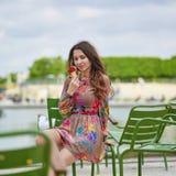 Νέα παρισινή γυναίκα που τρώει το παγωτό στοκ φωτογραφίες