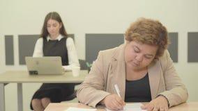 Νέα παχουλή γυναίκα αφροαμερικάνων που γράφει κάτω τη συνεδρίαση πληροφοριών στο σύγχρονο γραφείο στο πρώτο πλάνο ενώ αυτή φιλμ μικρού μήκους