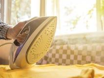 Νέα περιστασιακά ενδύματα σιδήρου εφήβων που χρησιμοποιούν τον ατμό ενάντια στο άμεσο φως του ήλιου στο σπίτι στοκ φωτογραφία με δικαίωμα ελεύθερης χρήσης