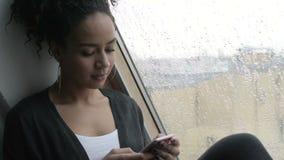 Νέα περιστασιακή γυναίκα που χρησιμοποιεί το κινητό τηλέφωνο απόθεμα βίντεο
