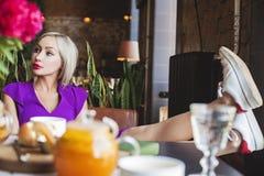 Νέα περιστασιακή χαλάρωση γυναικών στα λουλούδια καφέδων wirh στοκ εικόνα με δικαίωμα ελεύθερης χρήσης