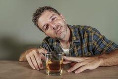Νέα πιωμένη και το οινοπνευματώδες σπαταλημένο άτομο γυαλί ουίσκυ κατανάλωσης που μέθησαν και ακατάστατο στο σκοτεινό υπόβαθρο στ στοκ εικόνες με δικαίωμα ελεύθερης χρήσης