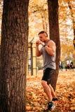 Νέα προκλητικά χτυπήματα άσκησης αθλητών σε ένα δέντρο στο πάρκο στοκ φωτογραφία