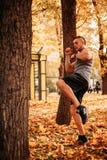 Νέα προκλητικά χτυπήματα άσκησης αθλητών σε ένα δέντρο στο πάρκο στοκ εικόνες