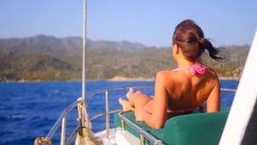 Νέα προκλητική γυναίκα που κάνει ηλιοθεραπεία στο γιοτ πολυτέλειας απόθεμα βίντεο