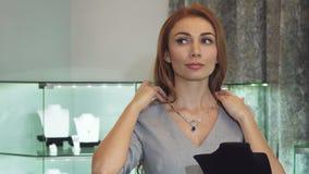 Νέα προκλητική γυναίκα που προσπαθεί στο περιδέραιο διαμαντιών στο κατάστημα κοσμήματος απόθεμα βίντεο