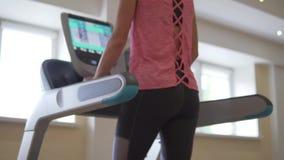 Νέα προκλητική γυναίκα που τρέχει treadmill προσομοιωτών στην αίθουσα απόθεμα βίντεο