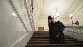 Νέα προκλητική γυναίκα brunette στο μαύρο φόρεμα βραδιού που πηγαίνει επάνω στη μαρμάρινη σκάλα πετρών στο παλάτι ή το ξενοδοχείο απόθεμα βίντεο