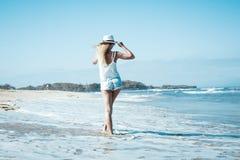 Νέα προκλητική γυναίκα με το άσπρο καπέλο που περπατά στην άσπρη παραλία άμμου ένα τροπικό νησί του Μπαλί στην ηλιόλουστη ημέρα Ω Στοκ Φωτογραφίες