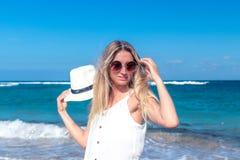 Νέα προκλητική γυναίκα με το άσπρο καπέλο που περπατά στην άσπρη παραλία άμμου ένα τροπικό νησί του Μπαλί στην ηλιόλουστη ημέρα Ω Στοκ Εικόνα