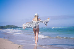 Νέα προκλητική γυναίκα με το άσπρο καπέλο που περπατά στην άσπρη παραλία άμμου ένα τροπικό νησί του Μπαλί στην ηλιόλουστη ημέρα Ω Στοκ Εικόνες