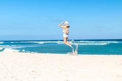 Νέα προκλητική γυναίκα με το άσπρο σακίδιο πλάτης καπέλων και πολυτέλειας snakeskin python που πηδά στην άσπρη παραλία άμμου ένα  Στοκ Εικόνες