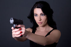 Νέα προκλητική γυναίκα που στοχεύει με το πυροβόλο όπλο πέρα από το γκρι Στοκ Φωτογραφία