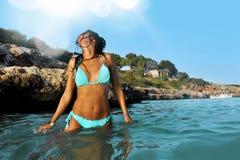 Νέα προκλητική γυναίκα στο μπλε μπικίνι στην παραλία που έχει ένα λουτρό στη θάλασσα από τους βράχους που απολαμβάνουν το καλοκαί Στοκ Φωτογραφία