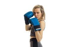 Νέα προκλητική ξανθή τοποθέτηση στη κάμερα στα μπλε εγκιβωτίζοντας γάντια Στοκ Φωτογραφία