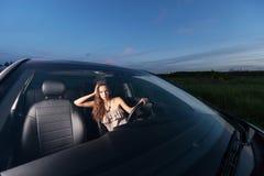 Νέα προκλητική συνεδρίαση γυναικών πίσω από τη ρόδα ενός αυτοκινήτου και της εξέτασης τη κάμερα υπαίθρια Στοκ Εικόνα