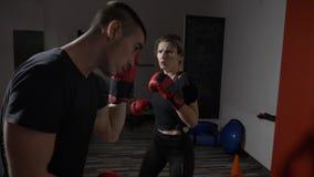 Νέα πρότυπη λήψη γυναικών σπουδαστών μόνη - αμυντικά μαθήματα από έναν επαγγελματικό αρσενικό μπόξερ σε ένα αθλητικό στούντιο γυμ απόθεμα βίντεο