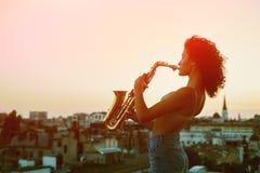Νέα πρότυπη τοποθέτηση γυναικών στη στέγη της οικοδόμησης που κρατά ένα saxophone Στοκ φωτογραφία με δικαίωμα ελεύθερης χρήσης