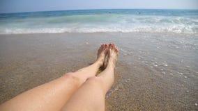 Νέα πόδια γυναικών που κάνουν ηλιοθεραπεία στην παραλία φιλμ μικρού μήκους