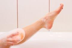 Νέα πλύση γυναικών με το σφουγγάρι στο λουτρό Στοκ Εικόνα