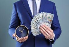Νέα ρολόι και χρήματα εκμετάλλευσης επιχειρηματιών Στοκ φωτογραφία με δικαίωμα ελεύθερης χρήσης