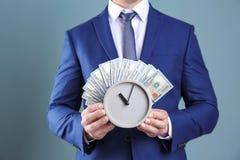 Νέα ρολόι και χρήματα εκμετάλλευσης επιχειρηματιών Στοκ εικόνες με δικαίωμα ελεύθερης χρήσης
