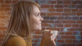 Νέα ρομαντική γυναίκα ομορφιάς που πίνει τον καυτό καφέ στον καφέ Ευτυχές χαλαρωμένο κορίτσι που απολαμβάνει το φλυτζάνι του θερμ απόθεμα βίντεο