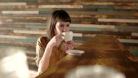 Νέα ρομαντική γυναίκα ομορφιάς που πίνει το καυτό τσάι ή τον καφέ στο φως πρωινού Ευτυχές χαλαρωμένο κορίτσι που απολαμβάνει το φ φιλμ μικρού μήκους