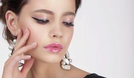 Νέα σκέψη θηλυκός με τα λαμπρά σκουλαρίκια στοκ εικόνα