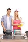 Νέα σκουπίζοντας πιάτα ζευγών από κοινού Στοκ Φωτογραφίες