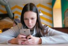 Νέα σοβαρά ανάγνωση γυναικών κάτι στην κινητή τηλεφωνική συνεδρίασή της στον καφέ Στοκ φωτογραφία με δικαίωμα ελεύθερης χρήσης